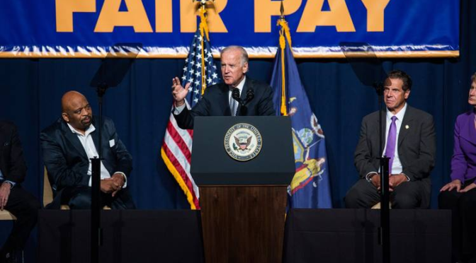 "President Biden speaking at a podium in front of a sign that says ""Fair Pay"""
