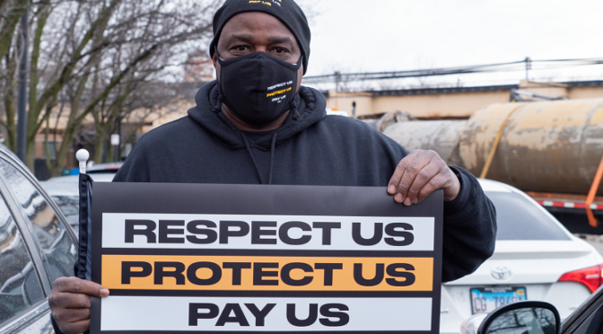 """Man holding sign that says """"Respect Us. Protect Us. Pay Us."""""""