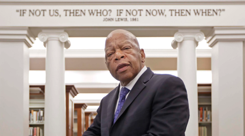 """John Lewis, standing in front of columns that say """"If not us, then who? If not now, then when?"""""""